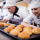 Male and female chefs preparing kaiser rolls in kitchen - PhotoDune Item for Sale