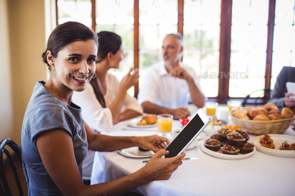 Businesswoman looking at camera while using digital tablet - Stock Photo - Images