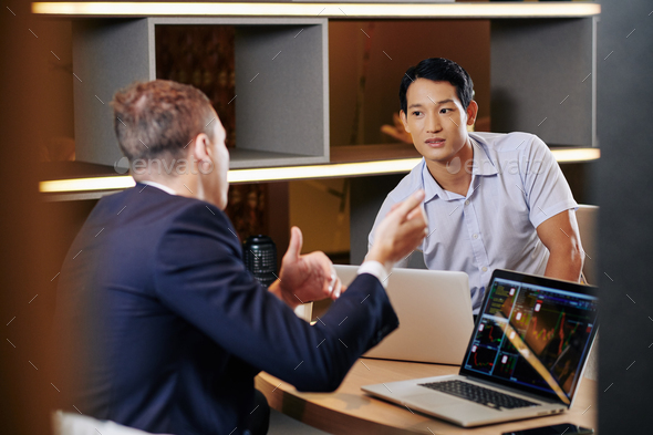 Businessman listening to coworker - Stock Photo - Images