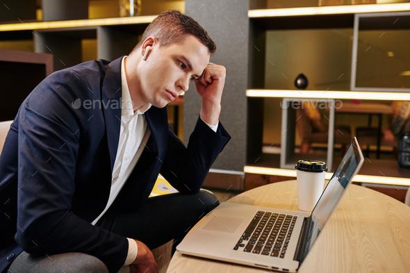 Pensive businessman reading e-mail - Stock Photo - Images