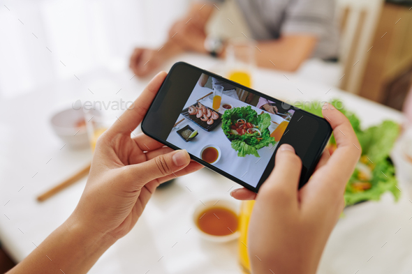 Woman photographing dishes - Stock Photo - Images