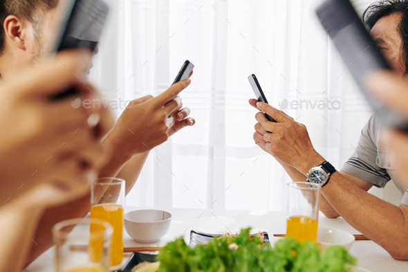 Family members checking smartphones - Stock Photo - Images