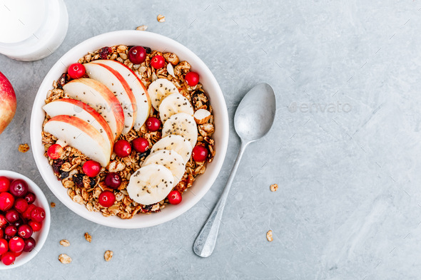 Healthy granola breakfast bowl with apple, cranberry, banana and chia seeds. Top view, copy space. - Stock Photo - Images