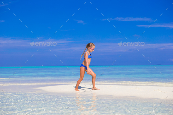 Adorable happy little girl have fun at shallow water on beach vacation - Stock Photo - Images