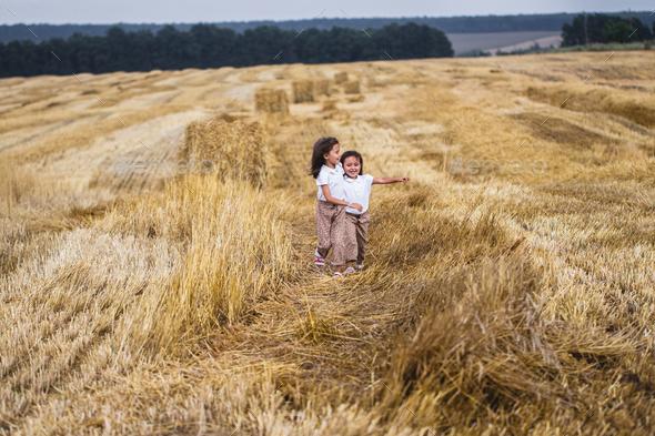 Little girl running across the sunny field - Stock Photo - Images