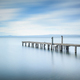 Wooden pier or jetty remains on a blue lake. Long Exposure. - PhotoDune Item for Sale