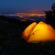 Orange lighted inside tent on mountain above city in night lights - PhotoDune Item for Sale