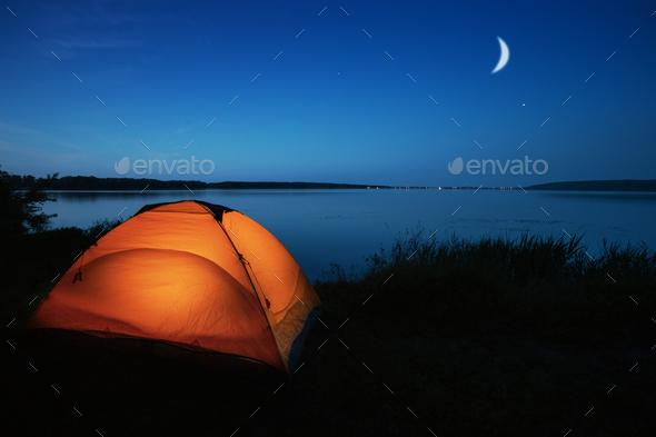 Orange tourist tent lit by a lake - Stock Photo - Images