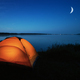 Orange tourist tent lit by a lake - PhotoDune Item for Sale