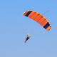 Skydiver under an orange parachute in blue sky - PhotoDune Item for Sale