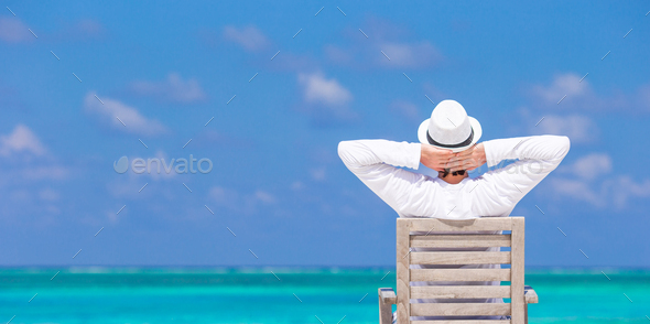 Young man enjoying summer vacation on tropical beach - Stock Photo - Images