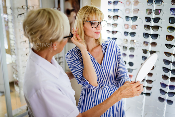 Health care, people, eyesight and vision concept. Woman with optician choosing glasses - Stock Photo - Images