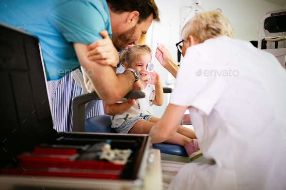 Ophthalmologist, optometrist checking child vision looking for problems and caring for eye - Stock Photo - Images