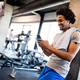 Young muscular man using mobile phone at the gym in exercise break - PhotoDune Item for Sale