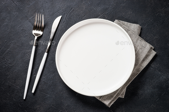 White plate, cutlery and napkin on black table top view - Stock Photo - Images