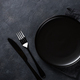 Black plate, cutlery and napkin on stone table top view - PhotoDune Item for Sale