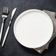 White plate, cutlery and napkin on black table top view - PhotoDune Item for Sale