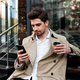 Young handsome casual man in trench coat with coffee to go thoughtfully using cellphone on street - PhotoDune Item for Sale