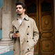 Young confident man in trench coat walking through city street with coffee to go - PhotoDune Item for Sale
