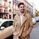 Young attractive smiling stylish man in trench coat happily walking through street - PhotoDune Item for Sale