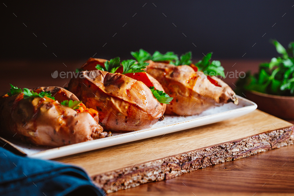 Baked three sweet potatoes with fresh parsley on a white ceramic dish - Stock Photo - Images