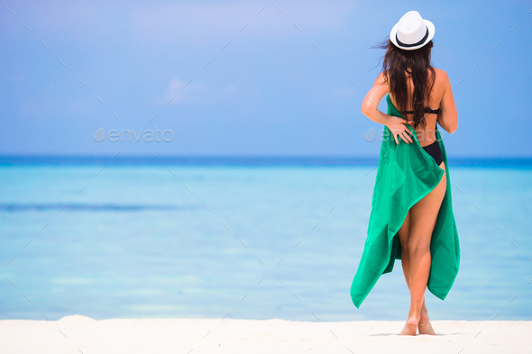 Young woman with green beach towel during tropical vacation - Stock Photo - Images