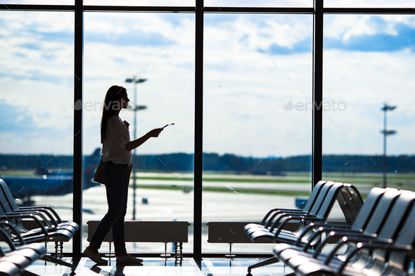 Silhouette of woman in an airport lounge waiting for flight aircraft - Stock Photo - Images