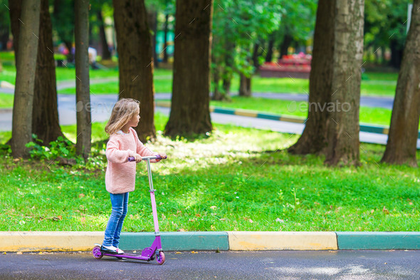 Adorable little girl have fun on the scooter outdoor - Stock Photo - Images