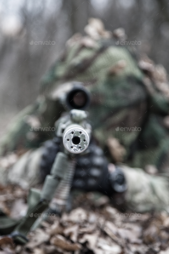 Sniper shooting from masked position on ground - Stock Photo - Images