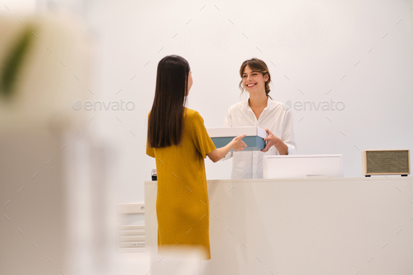 Young smiling fashion consultant joyfully giving box with clothes to customer in fashion store - Stock Photo - Images