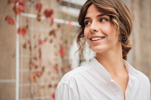 Young attractive stylish woman happily looking away in workshop - Stock Photo - Images