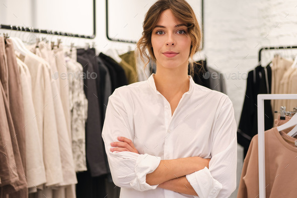 Young attractive woman in shirt holding hands crossed confidently looking in camera in clothes store - Stock Photo - Images