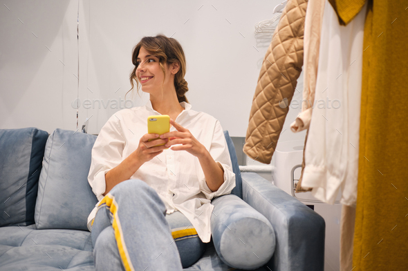 Young fashion consultant happily using cellphone on sofa in showroom - Stock Photo - Images