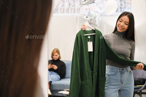 Attractive stylish Asian girl happily choosing cardigan in fashion store - Stock Photo - Images