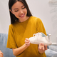 Beautiful smiling Asian girl happily holding white sneaker in hands in fashion store - PhotoDune Item for Sale