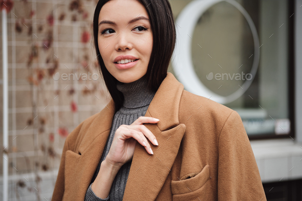 Portrait of beautiful Asian girl in coat dreamily looking away outdoor - Stock Photo - Images