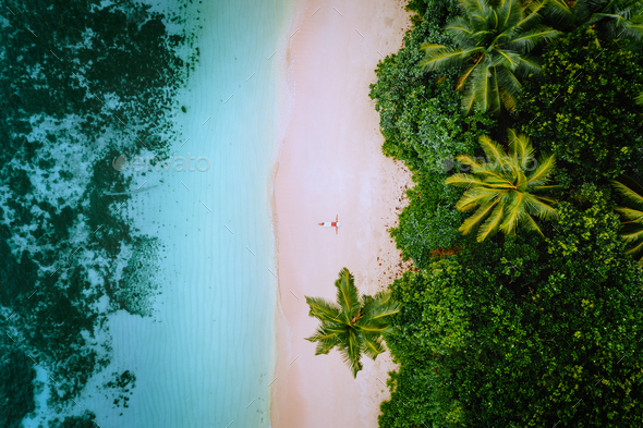 Aerial view of a young woman relaxing on the tropical paradise sandy beach surrounded by palm trees - Stock Photo - Images