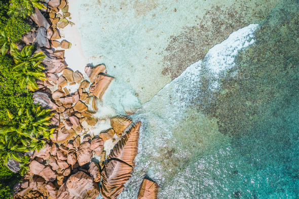 Aerial top view of ocean waves hitting granite rocks on the tropical beach in La Digue, Seychelles - Stock Photo - Images