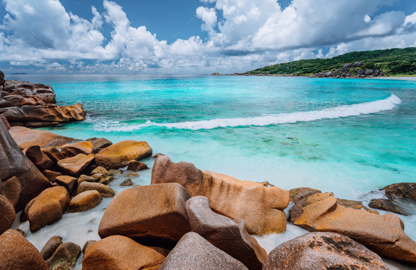 Rolling wave and stunning granite formations on the beautiful tropical island with white clouds of - Stock Photo - Images