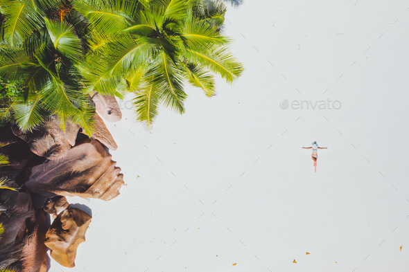 Aerial photo of young woman laying on exotic tropical beach with white sand. Girl sunbathing and - Stock Photo - Images