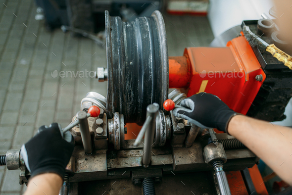 Mechanic works with wheel on disc rolling machine - Stock Photo - Images