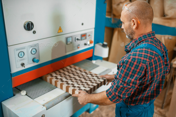 Carpenter works on woodworking machine, factory - Stock Photo - Images