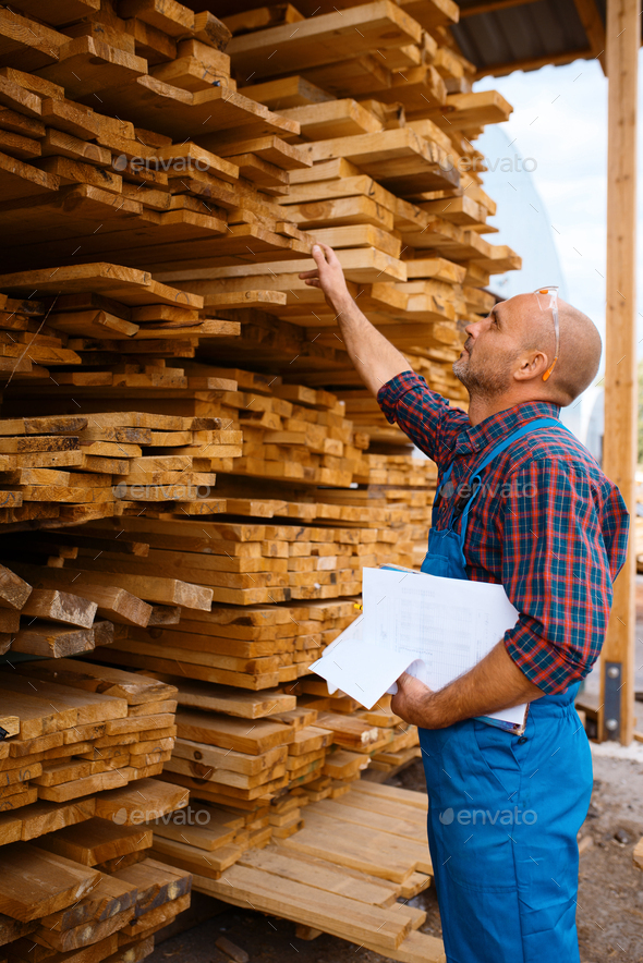 Carpenter in uniform check boards on sawmill - Stock Photo - Images