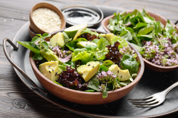 Clay dish with salad of avocado, green and violet lettuce - Stock Photo - Images