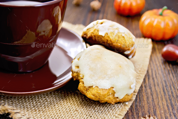 Cookies pumpkin with cup on sacking - Stock Photo - Images