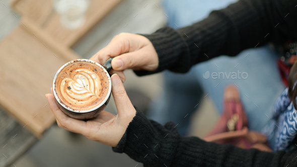 Coffee latte heart texture in hand of tourists. - Stock Photo - Images