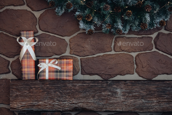 Wrapped Christmas presents on wooden pile. top of a fireplace under Christmas wreath - Stock Photo - Images