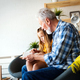 Happy little girl with grandfather reading story book at home - PhotoDune Item for Sale