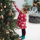 Cute little girl in red dress touching toy ball on Christmas tree at luxury home interior - PhotoDune Item for Sale