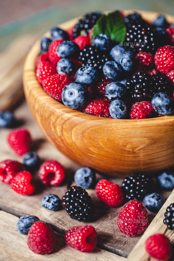 blueberries and raspberries, blackberry in a wooden bowl on old wood background - Stock Photo - Images